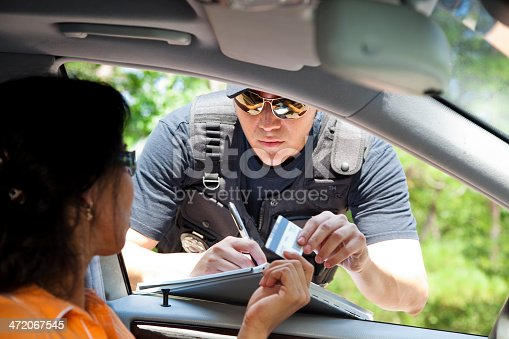 Policeman stops woman driver to give her a traffic ticket for speeding.  He takes her driver's license.