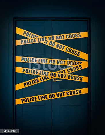 istock Crime scene closed door with yellow stripes text Police line do not cross 941403616