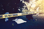 "Detective and his forensic team are in crime scene in woods. Place is marked around with yellow tape with ""do not cross"" sign on it. Detective is looking at the body, photographing details and clues of murder. His forensic team is in the background collecting samples of grass, branches and blood found far away from the body."