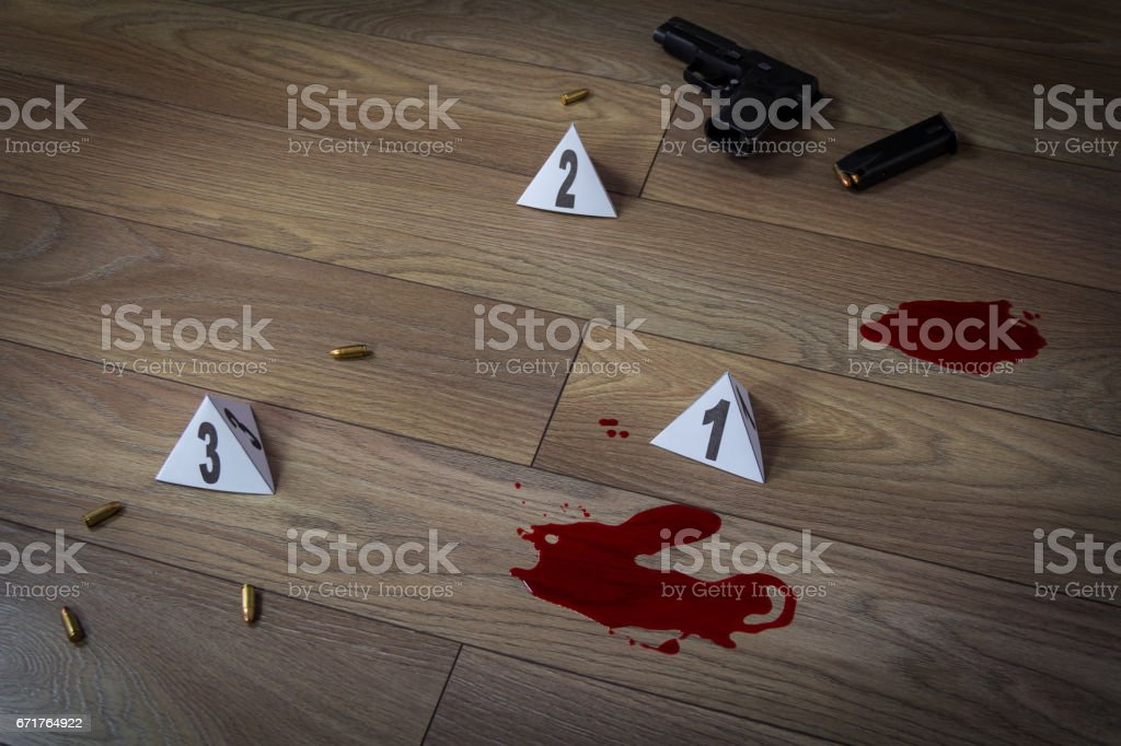 Crime scene indoors with traces of blood, handgun pistol and bullets stock photo