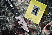 Crime scene investigation, Bloody knife and victim's shoes with criminal markers on ground, Homicide evidence.