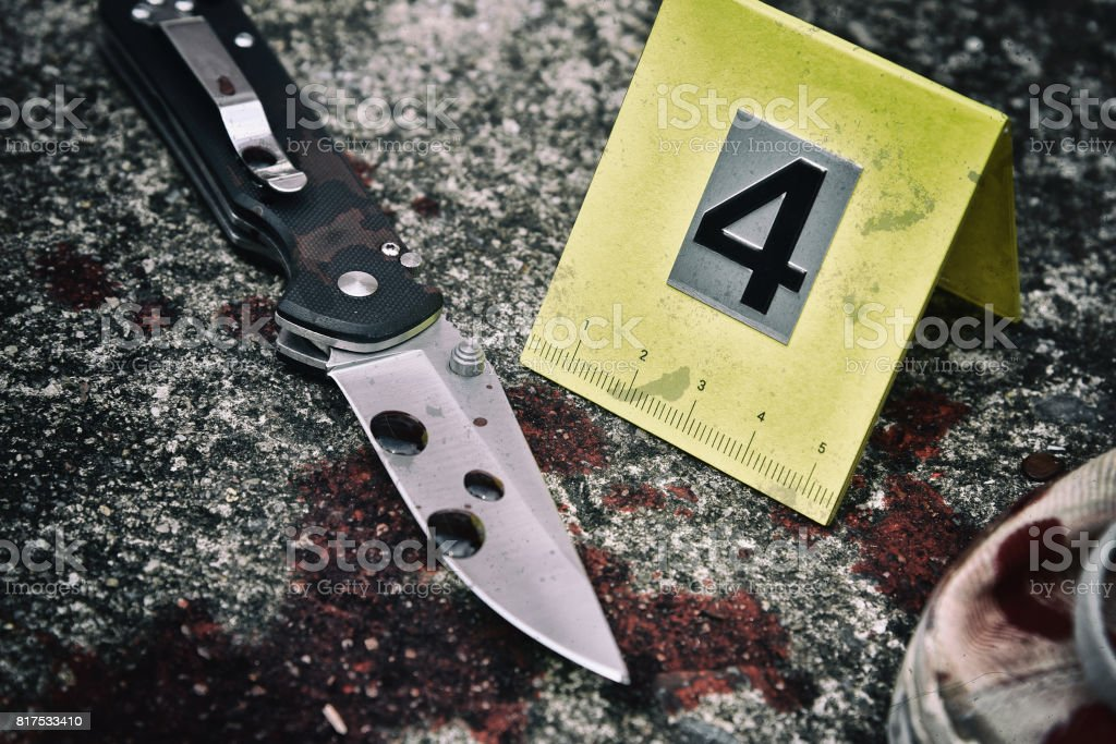 Crime scene investigation, Bloody knife and victim's shoes with criminal markers on ground stock photo