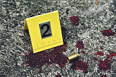 Crime scene investigation, Bullet shell with blood stain against the crime marker on the ground. (Selective Focus)