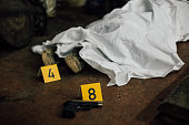 A photo showing covered dead body and founded evidence while investigating a crime scene.