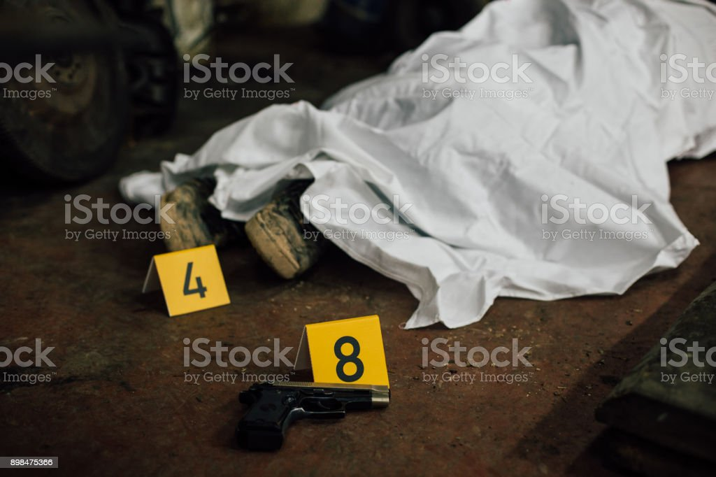 Crime scene investigation - covered human body and evidences stock photo