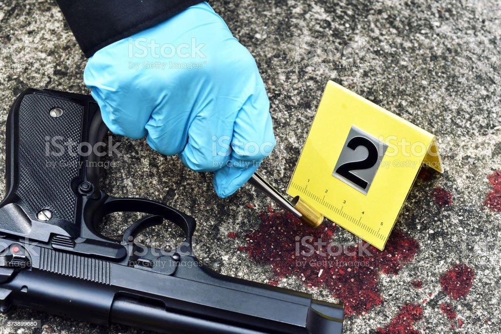 Tätern, Detektiv sammeln Kugel Schale mit Blut beflecken gegen die Kriminalität-Markierung. – Foto
