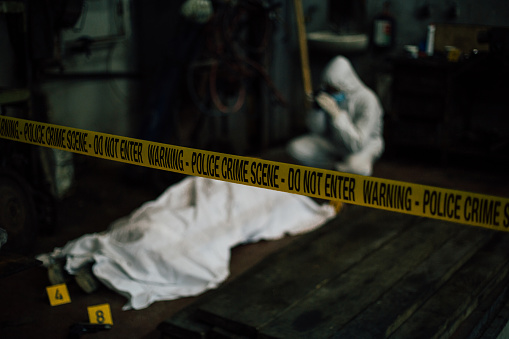 A blurred image of a forensic investigating a crime scene - covered dead body and evidence