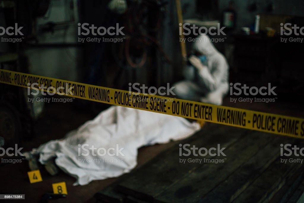 Investigação da cena do crime - forense investiga atrás de provas e o corpo de cobertura morta - foto de acervo