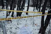 Blurred image of a forensic taking photo of a victim and evidence in a crime scene investigation.