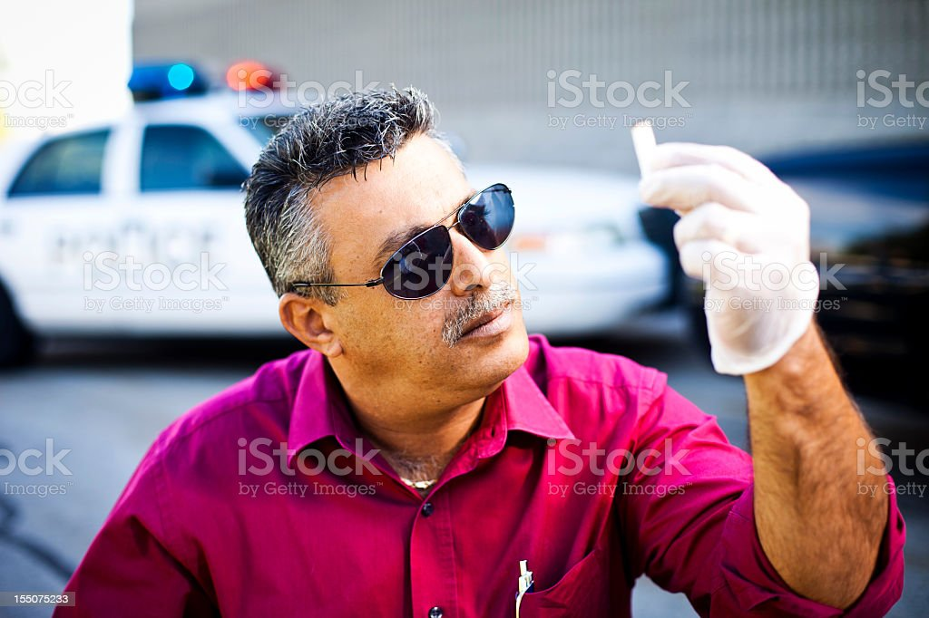 Crime Scene Investigator Looking at Evidence stock photo