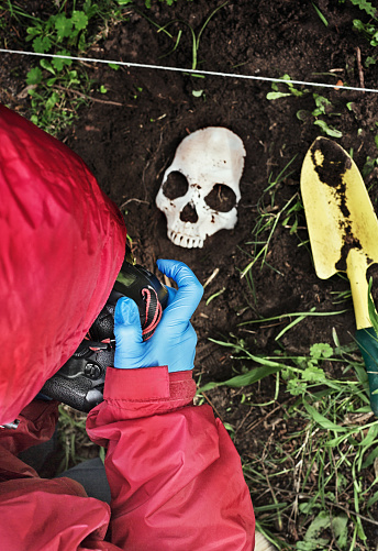 Cropped rear view of a crime technician taking a photograph of a partly unearthed human skull.