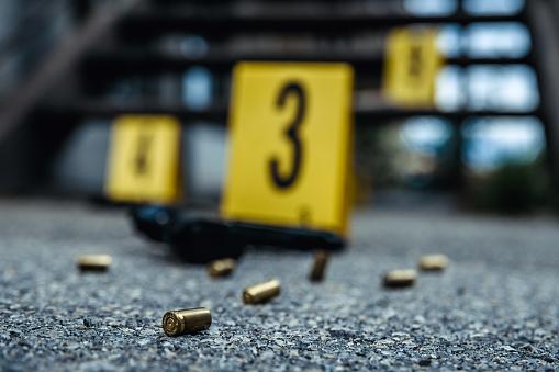 Bullet casings and gun on asphalt. Crime scene.