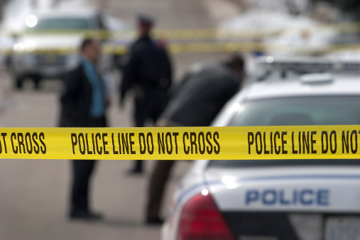 Long lens, crime scene. Detectives and officer in background.