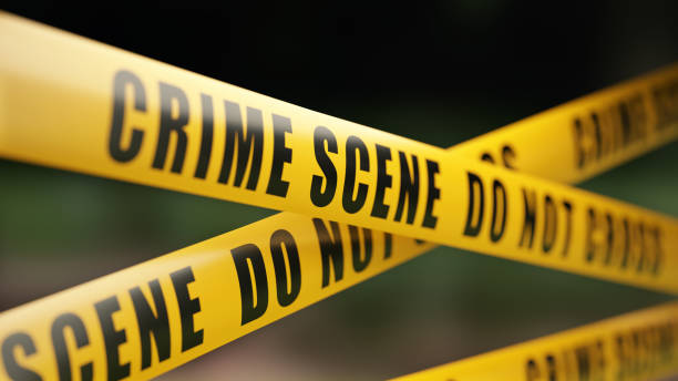 Crime Scene Tape Barrier In Front Of Defocused Background Yellow crime scene do not cross barrier tape in front of defocused background. Horizontal composition with selective focus and copy space. crime stock pictures, royalty-free photos & images