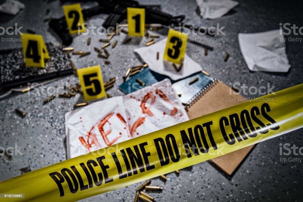 Crime scene tape blocks off a notebook with HELP! written in blood and crime scene markers after a school shooting in America. stock photo