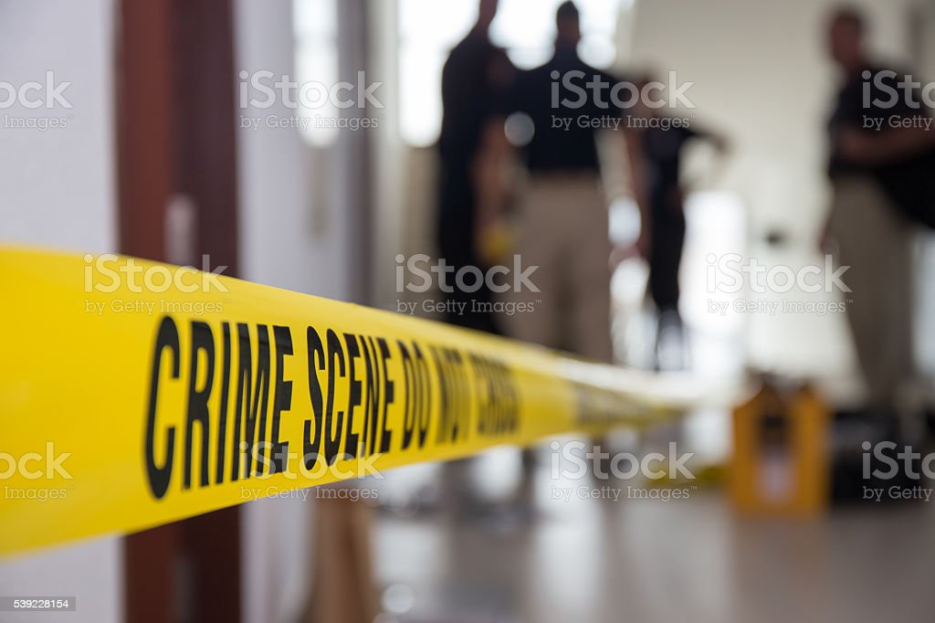 crime scene tape in building with blurred forensic team stock photo