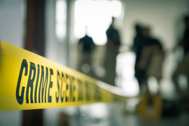 crime scene tape with blurred forensic in cinematic tone crime scene tape with blurred forensic law enforcement background in cinematic tone and copy space crime stock pictures, royalty-free photos & images