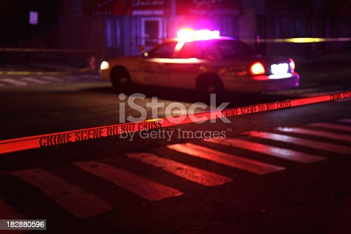 Police car and crime scene tape on a city street