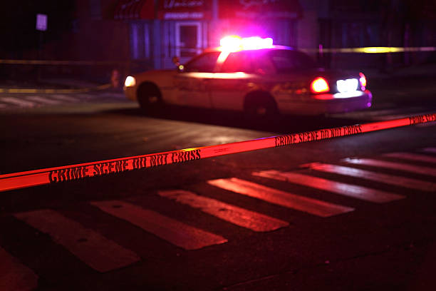 Crime Scene with Police Car Police car and crime scene tape on a city street crime stock pictures, royalty-free photos & images