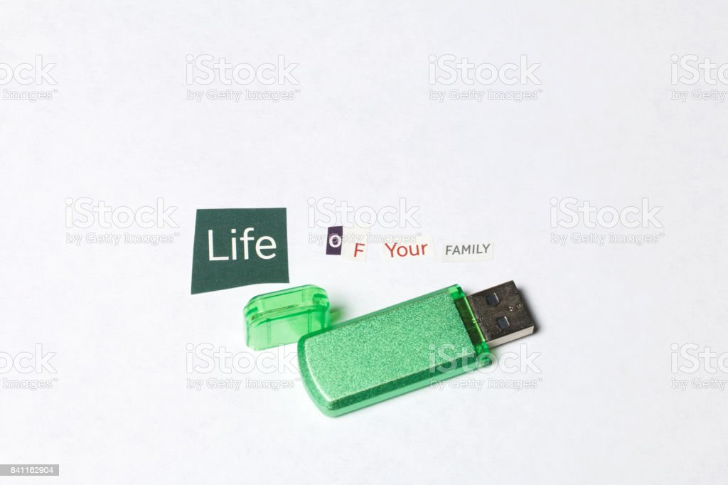 Criminal activity. Preparation of a letter with threats. Letters cut from different editions are pasted onto a white sheet of paper. They make up an unfinished letter. Next to the flash drive with information. stock photo