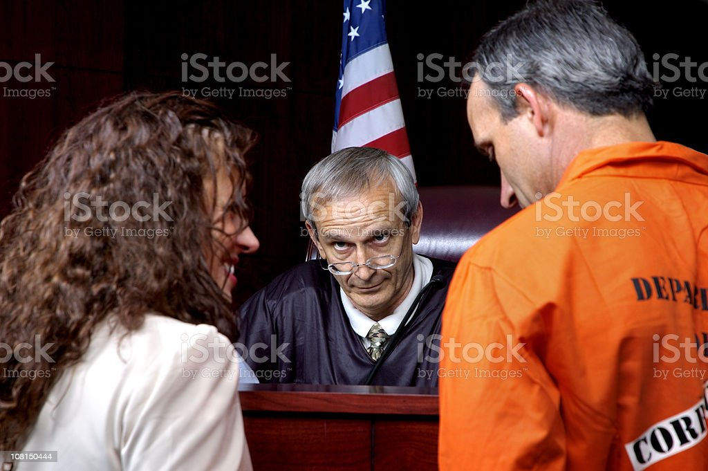 Criminal and Lawyer Standing in Front of Judge stock photo