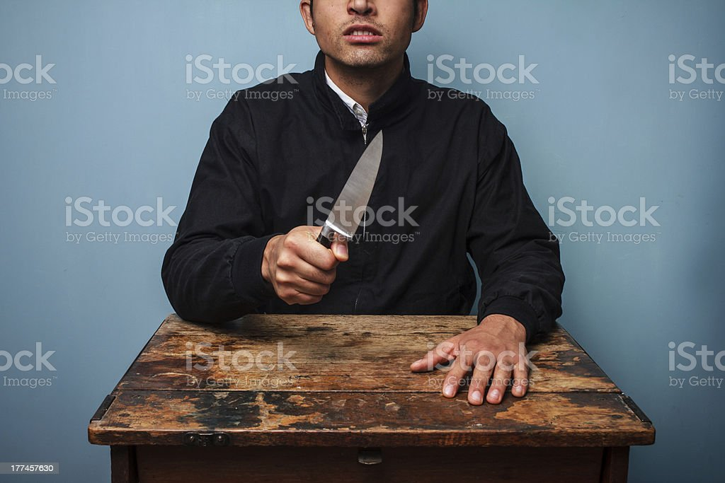 Criminal at table wielding a knife royalty-free stock photo