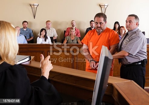 A criminal defendant standing before the judge in a courtroom.