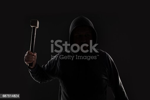 istock Criminal in dark clothes and balaclava with hammer 687514824