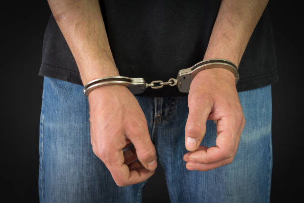 criminal in handcuffs arrested for crimes in his home - boy handcuffs stock pictures, royalty-free photos & images