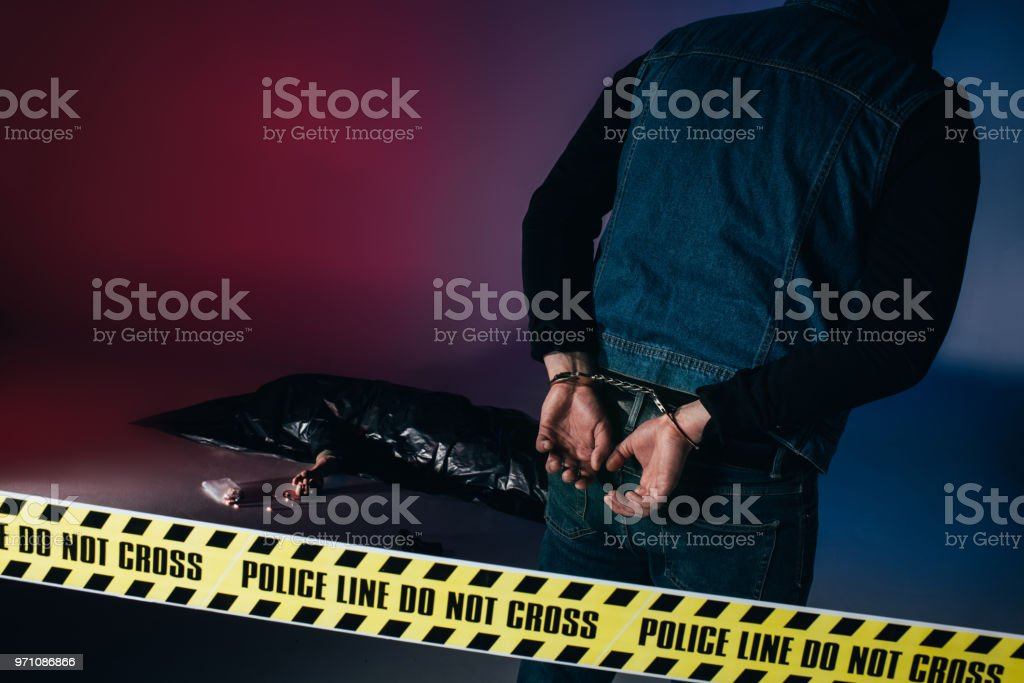 Criminal in handcuffs by body in trash bag behind police tape on dark background stock photo