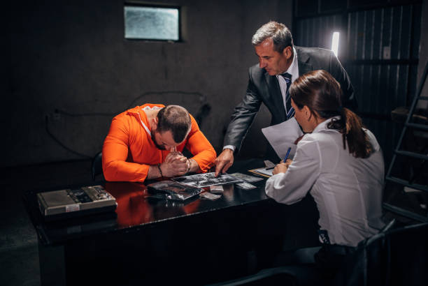 Criminal Investigation Man with handcuffs and two detectives/lawyer sitting in the investigation room police interview stock pictures, royalty-free photos & images