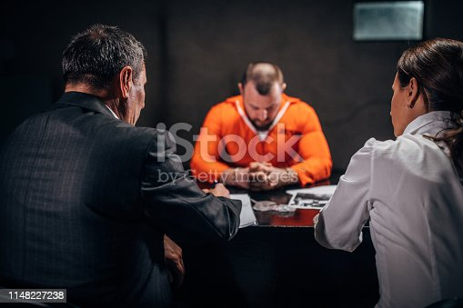 Man with handcuffs and two detectives/lawyer sitting in the investigation room