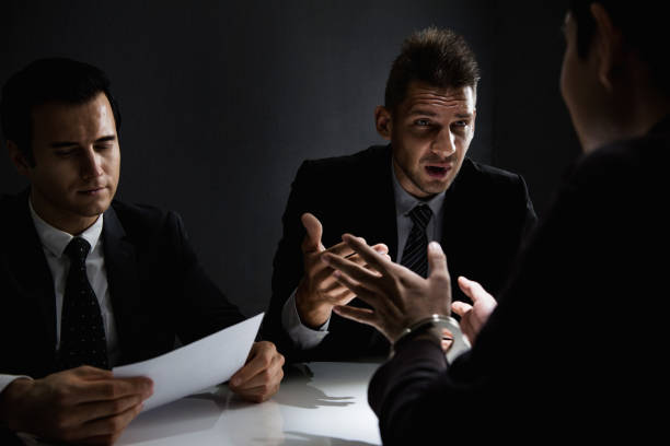 Criminal man being interviewed in interrogation room after committed a crime Suspect or criminal man with handcuffs being interviewed by detectives in interrogation room after committed a crime police interview stock pictures, royalty-free photos & images