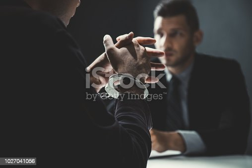 Criminal man with handcuffs being interviewed in interrogation room after committed a crime
