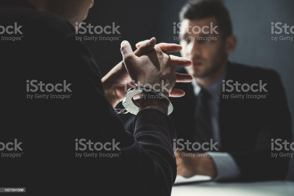 Kriminelle Mann mit Handschellen interviewt im Verhörraum – Foto