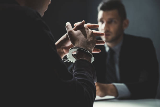 Criminal man with handcuffs being interviewed in interrogation room Criminal man with handcuffs being interviewed in interrogation room after committed a crime criminal stock pictures, royalty-free photos & images