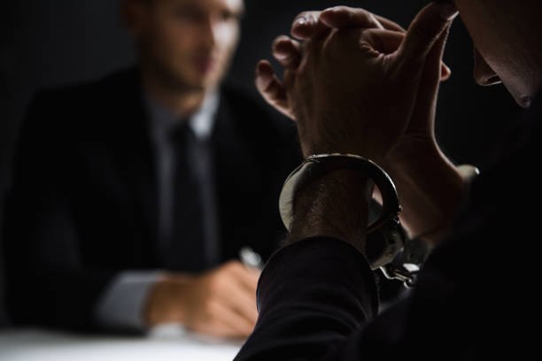 Criminal man with handcuffs in interrogation room Criminal man with handcuffs in interrogation room feeling guilty after committed a crime police interview stock pictures, royalty-free photos & images