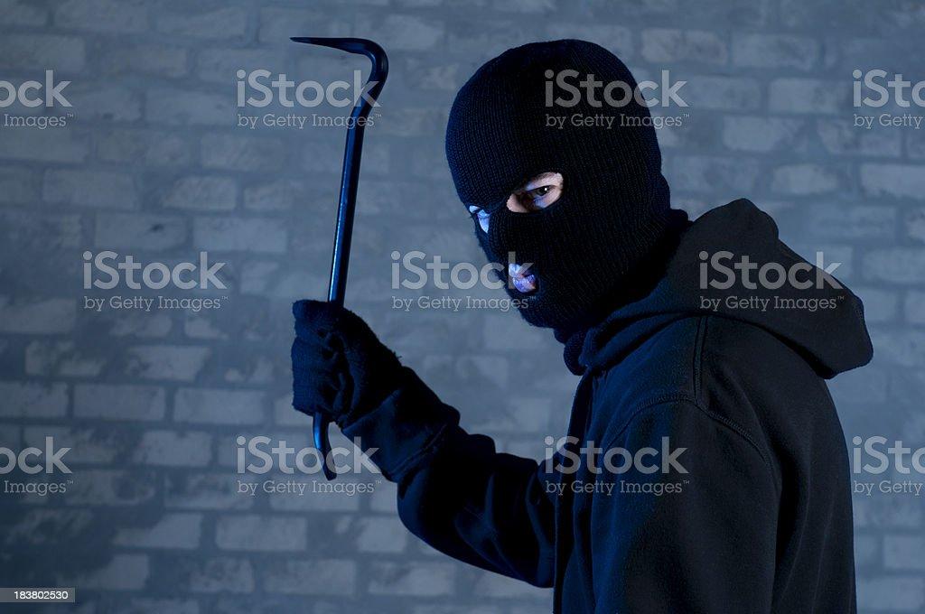 Criminal raises crowbar ready to hit stock photo