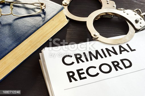 Criminal record and handcuffs on a desk.