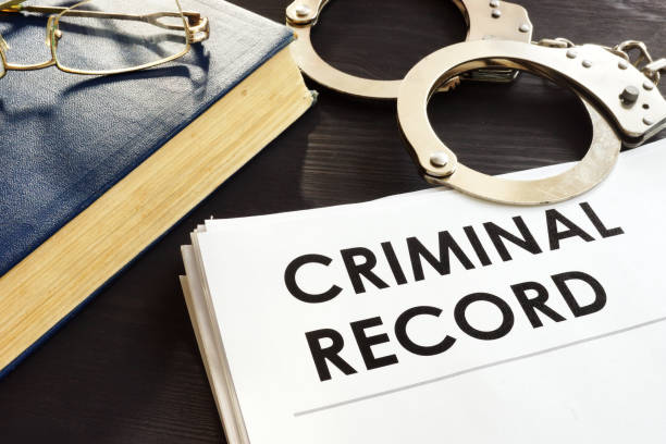 Criminal record and handcuffs on a desk. Criminal record and handcuffs on a desk. album stock pictures, royalty-free photos & images