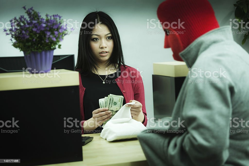 Criminal Robber Robbing an Asian Retail Bank Teller at Counter stock photo