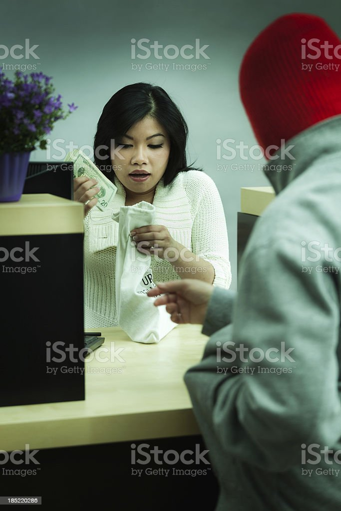 Criminal Robber Robbing Asian Retail Bank Teller at Counter Vt stock photo