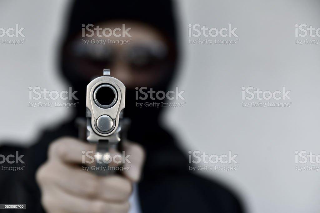 Criminal robber with aiming gun, Bad guy in hood holding pistol handgun. stock photo