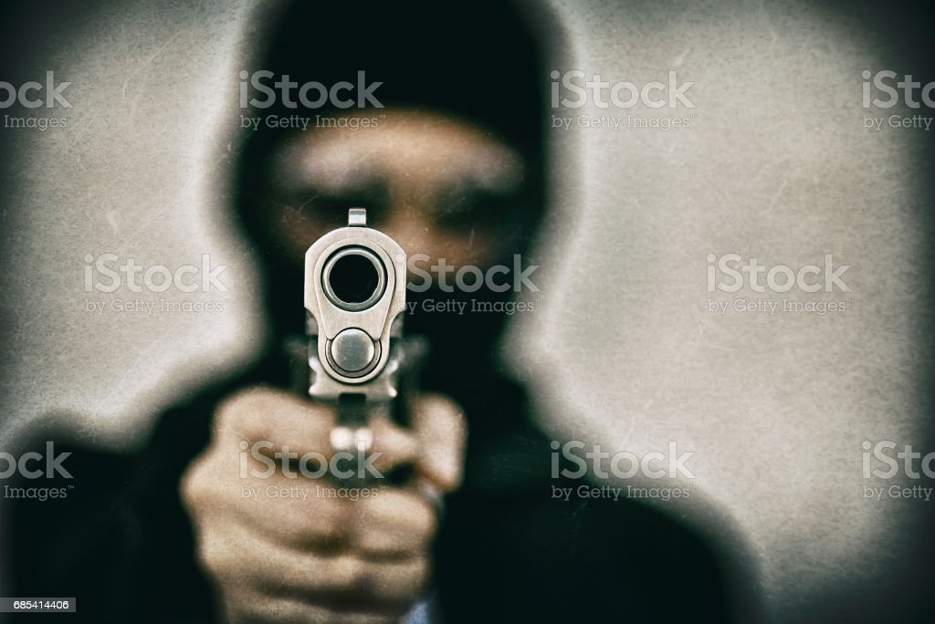 Criminal robber with aiming gun, Bad guy in hood holding pistol handgun. foto de stock royalty-free