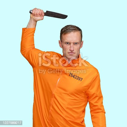 istock Criminal standing in front of blue background wearing jumpsuit and holding weapon 1227589217