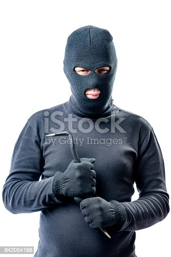 istock Criminal with a crowbar in hands in a black balaclava posing against a white background 842054168