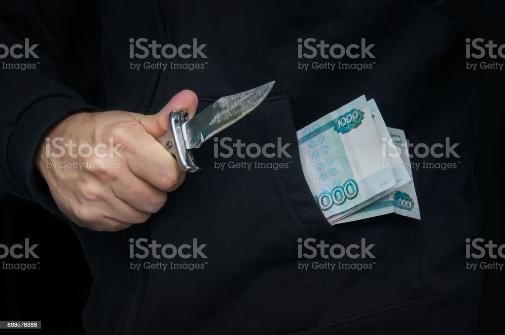 A criminal with a knife in his hand and Russian money in your pocket. stock photo