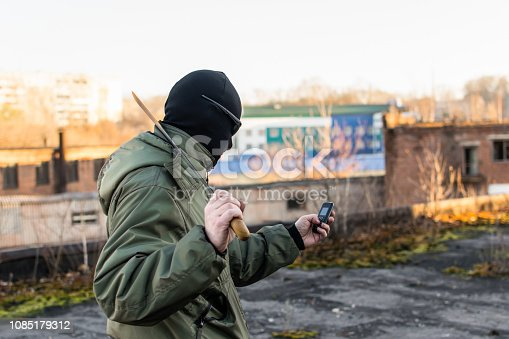 The criminal in a mask and a large knife writes a message in the phone