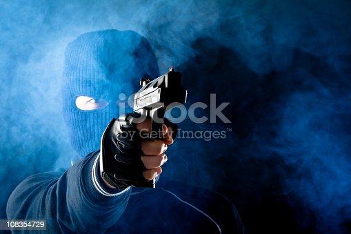 Criminal wearing a balaclava and aiming a gun. Grainy added
