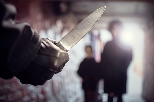Criminal with knife weapon threatening woman and child in underpass crime